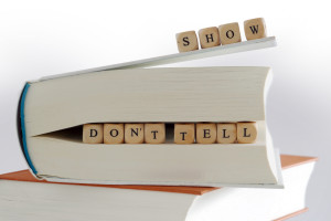 "message ""show don't tell"" for creativ writing, spelled with wooden letter blocks on the top and between pages of a  book"